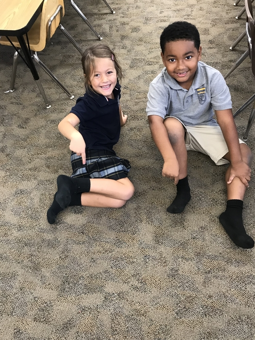 When the Kindergarteners receive 25 or more Pom Poms in their bucket they are able to choose a reward. These two students chose to take their shoes off in class. Congratulations to these two for working so hard and choosing kindness with their peers.